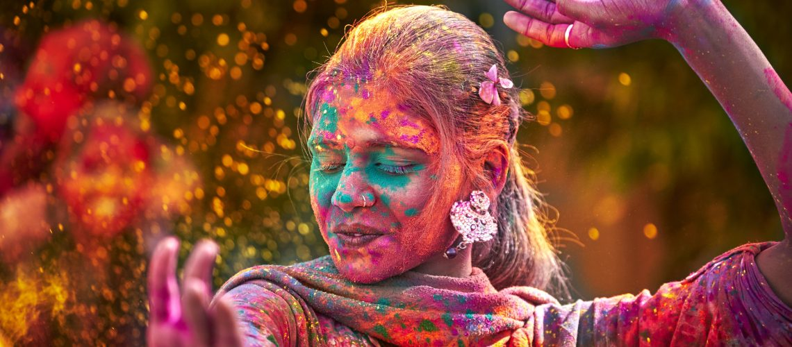 Portrait Of Young Indian Woman With Colored Face Dancing During Holi